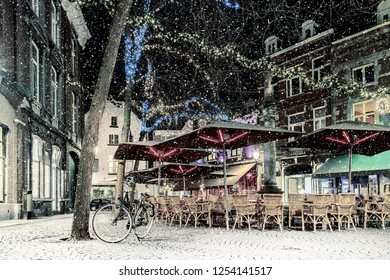 Bars and restaurants with christmas lights on the Sint Amorsplein square in Maastricht during snowfall, The Netherlands