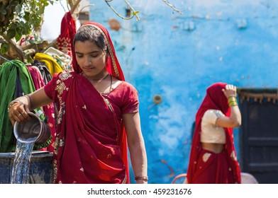 Barsana, India - March 09, 2014 : Village girl in red pouring water as her daily chore at Barsana village, District Mathura, Uttar Pradesh, India