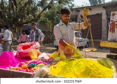 Barsana, India - March 17, 2016: Unidentified man sell colorful powdered dyes used for Holi festival in India