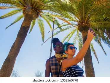 Barselona, Spain .   August 25.2016  Euroafrican man and spanish girl -  Funny  selfie  under Palm trees . creative looks, hairstyle and sunglasses of Couple