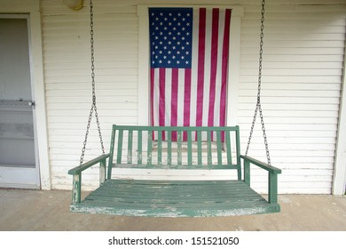 BARSTOW, CALIFORNIA - CIRCA 2005: Old swing on porch displaying an American Flag and patriotic theme near Barstow CA off Route 60