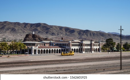 Barstow, California / USA - 19 Oct 2019: View across multiple rail tracks to Harvey House Railroad Depot. A yellow engineering train, white arched station, clear blue sky and mountains in the distance