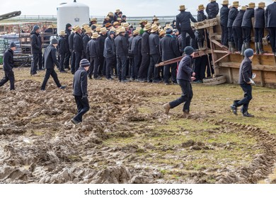 Bart, PA, USA - March 3, 2018: Amish walk through the muddy field at the annual Mud Sale at the Bart Fire Company.