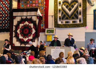 Bart, PA, USA - March 3, 2018: Assorted Amish-made quilts being auctioned as a fund raiser for the local fire company at a mud sale in Lancaster County, Pennsylvania.