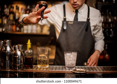 Bartender adding an alcoholic essence from a small glass bottle into the mixing glass on the bar counter