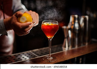 Bartender is adding lemon zest to the red cocktail at bar counter