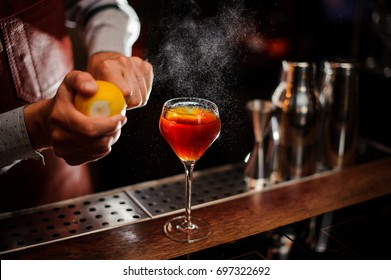 Bartender is adding lemon zest to the red cocktail at bar counter. Selective focus