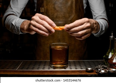 Bartender adding an orange zest juice to a golden cocktail in the glass with one stamped big ice cube on the bar counter in the dark blurred background in the dark