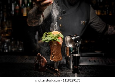 Bartender adding powder to a fresh summer cocktail with mint, orange and strawberries on the bar counter among the bartender equipment