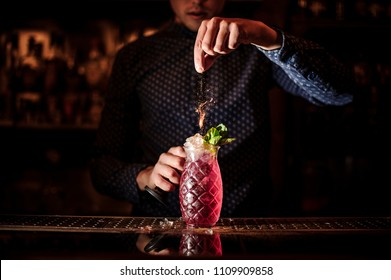 Bartender adding spices into the fresh and sweet strawberry mojito summer cocktail on the dark background