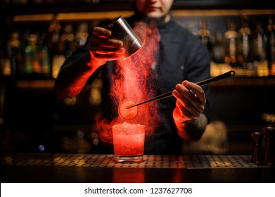 Bartender adding spices powder into a cocktail glass filled with a fresh strong alcoholic cocktail with slice of lemon