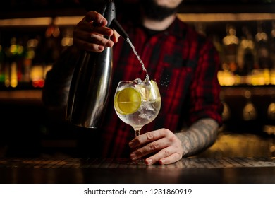 Bartender adding tonic water to the to the cocktail glass full of ice cubes with lime slices on the steel bar counter