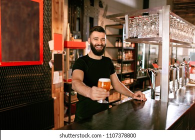 Bartender With Beer In Glass In Pub