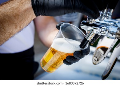 Bartender in black gloves pours beer into a disposable plastic glass.
