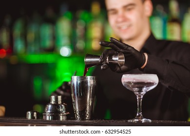 Bartender in black shirt making cocktail. Shallow depth of field.