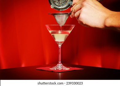Bartender carefully pouring a cocktail into a martini glass