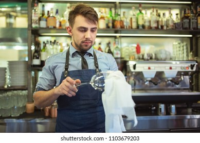 The bartender cleaning the glass on the bar
