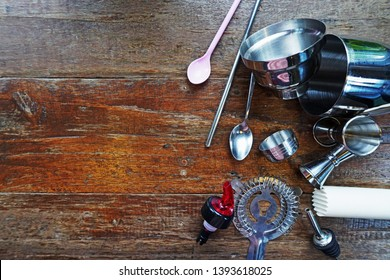 bartender cocktail equipment mixing with bar spoon, shaker, strainer,jigger, muddle and stainless steel straw on a wooden background, top view