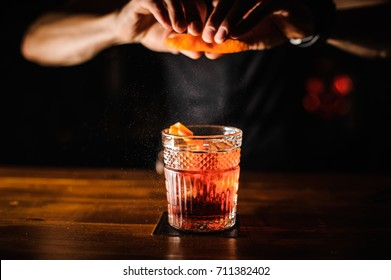 bartender with cocktail and orange peel preparing cocktail at bar. alcohol drinks, people and luxury concept