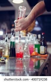 Bartender coocks cocktail behind a bar counter