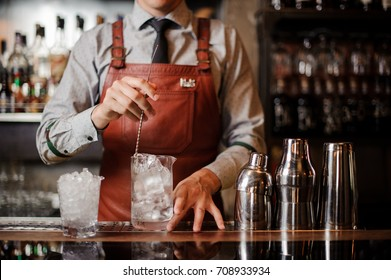 Bartender cooling out Cocktail glass mixing ice with a spoon no face