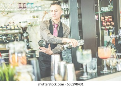 Bartender doing flair inside cruise american bar - Barman at work performing freestyle with bottle and shaker - Focus on man face - Bartending , cocktails and show entertainment concept - Retro filter