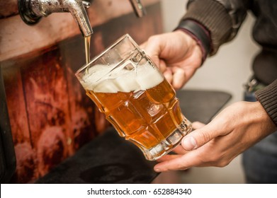 Bartender filling up with a blonde craft beer into a pint glass