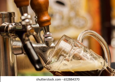 Bartender filling up a dark with craft beer a pint glass