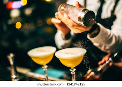 Bartender finishes preparation of cocktail in crystal glass by adding a bitter of powdered sugar. Close-up of expert bartender making cocktail in bar.