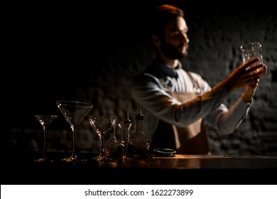 Bartender in the foreground of martini glasses, another cocktail glass and bottle with bitter on the bar counter in the blurred background in the dark