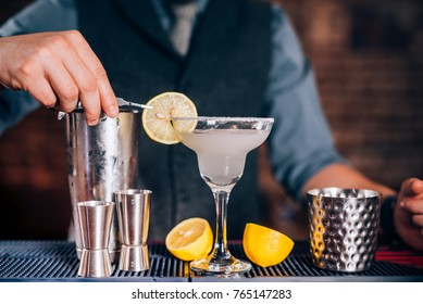 Bartender garnishing drink, pouring fresh lime margarita in fancy glass at restaurant