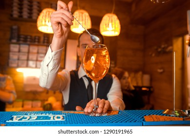 Bartender garnishing on the counter three Aperol Spritz, a classic refreshing Italian aperitif made mixing Aperol, Prosecco and sparkling soda to enjoy with friends and family at the bar before meals.