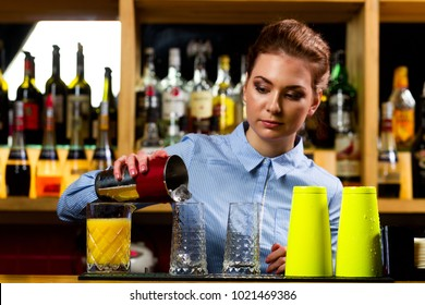 The bartender girl in the night bar at the bar prepares cocktails