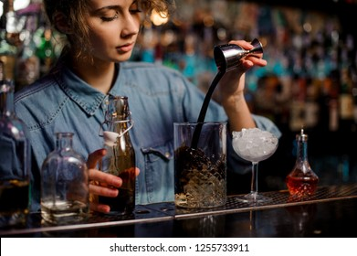 Bartender girl pouring to the measuring glass cup with ice cubes a brown alcoholic drink from steel jigger on the bar counter on the blurred background.