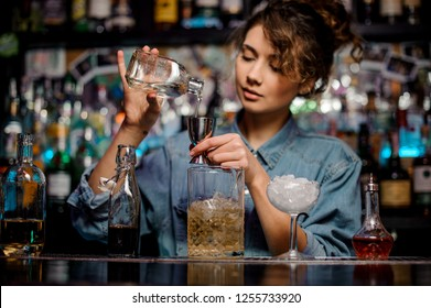 Bartender girl pouring to the steel jigger an alcoholic drink on the bar counter in the foreground of measuring cup, glass with ice and bottles