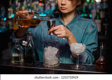 Bartender girl pouring to the steel jigger an alcoholic drink on the bar counter on the blurred background