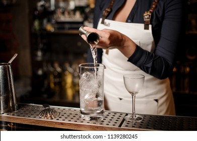 Bartender girl in the white apron adding an alcohol into the glass with ice cubes at the bar counter