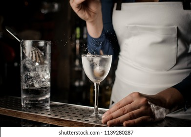 Bartender girl in the white apron throwing into the transparent cocktail one olive at the bar counter