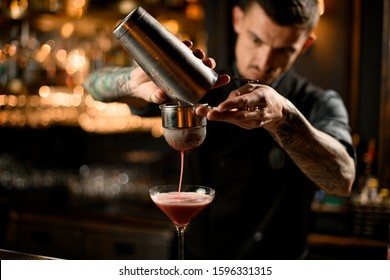 Bartender with goatee pouring tasteful cocktail from shaker through sieve