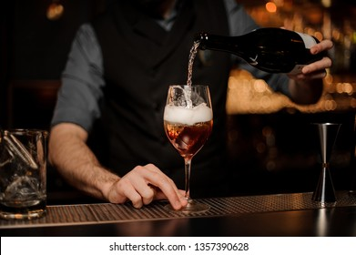 Bartender in gray shirt adds sparkling wine in cocktail on a black bar counter