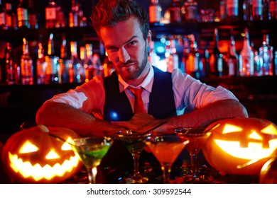 Bartender of Halloween night looking at pumpkin