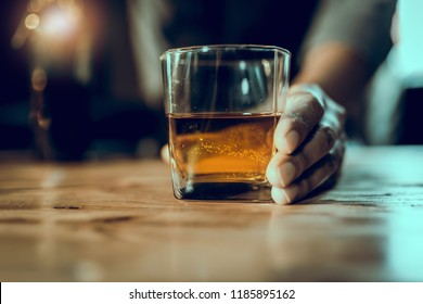Bartender hand, glass of whiskey on wood bar, bar out of focus,