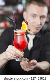 The bartender hands a freshly prepared cocktail to client