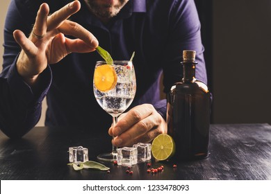bartender hands making Gin tonic mixed drink cocktail