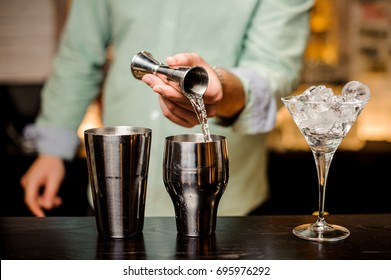 Bartender hands pouring alcoholic drink into a jigger to prepare a cocktail close up