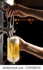 Bartender hands pouring a cold draft beer into a mug , black background. Pilsen - Shutterstock ID 1759558715