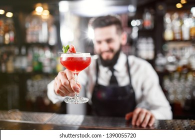 Bartender holding alcoholic cocktail. Barman giving glass forward. barman is making cocktail at night club.