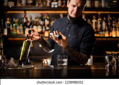 Bartender holding a bottle and pouring an alcoholic drink making a cocktail from the steel jigger to the glass on the bar counter