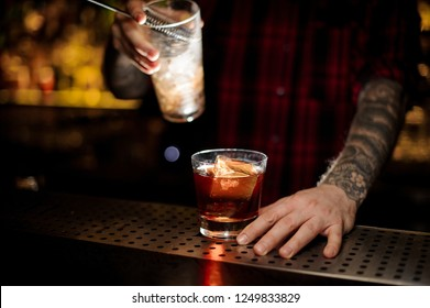 Bartender holding a Godfather cocktail and a measuring cup with the strainer on the bar counter on the blurred background
