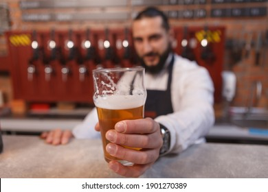 Bartender holding out beer glass to the camera, working at his pub